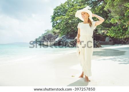 Beautiful woman wearing white dress, walking on a tropical beach - stock photo