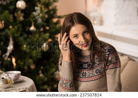 Beautiful woman wearing winter outfit sitting on couch at home near Christmas tree - stock photo