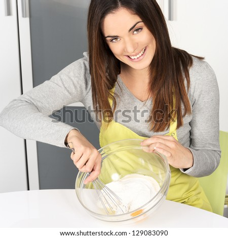 Beautiful woman whisking batter in kitchen - stock photo