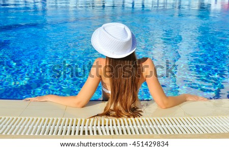 Beautiful woman white hat and bikini in a pool