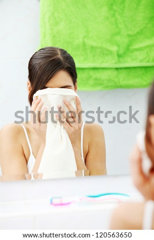 Beautiful woman wipes her face with a towel at bathroom