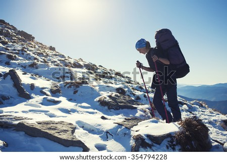 Beautiful woman with a backpack climbs the hill.