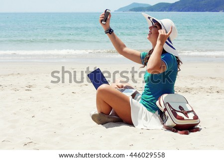 Beautiful woman with a bag working on laptop computer at beach