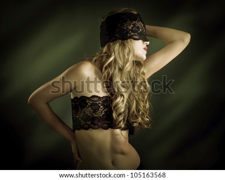 beautiful woman with a black lace on her eyes - stock photo
