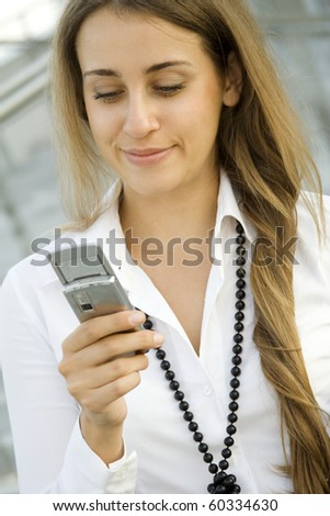Beautiful woman with a cell phone reads text messages, excited - stock photo