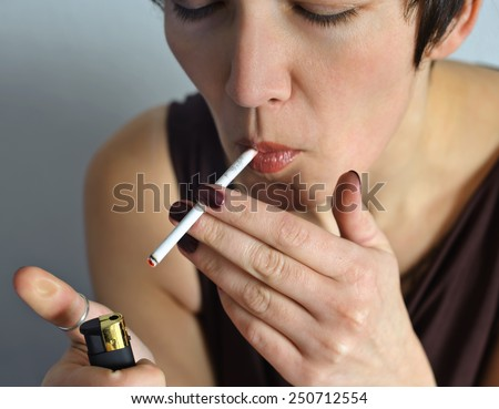 Beautiful woman with a cigarette. With one hand she holds a cigarette lighter other