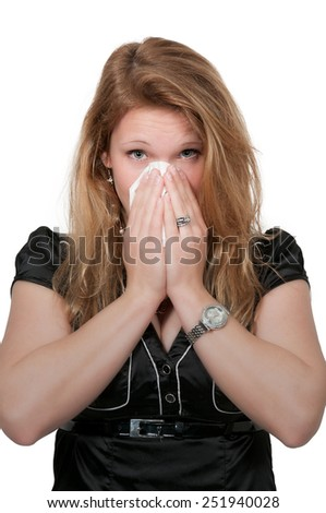 Beautiful woman with a cold, hay fever or allergies blowing her nose - stock photo