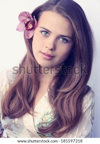 Beautiful woman with a flower in her hair - stock photo