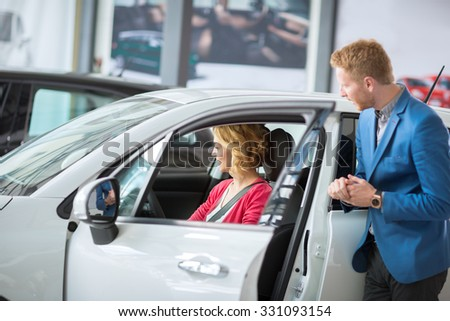 beautiful woman  with a friendly dealer car test new model - stock photo