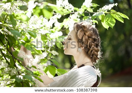 Beautiful woman with a hair braid and stylish make-up on the background of a blossoming park. - stock photo