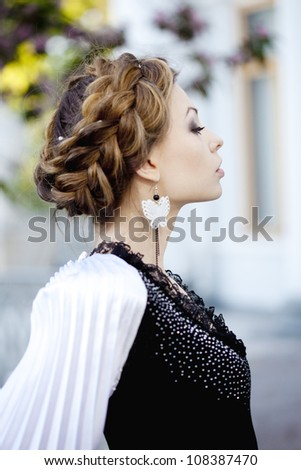 Beautiful woman with a hair braid and stylish make up on the background of a blossoming park. - stock photo
