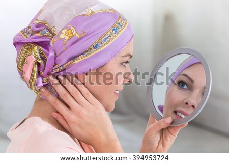 Beautiful woman with a headscarf looking  on mirror - stock photo