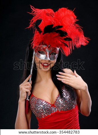 Beautiful woman with a mask in red dress on dark background