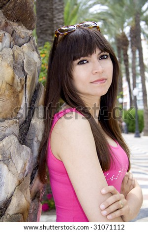Beautiful woman with a pink top leaning op against a palm tree