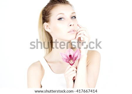 Beautiful woman with a proud look. Woman with clean and smooth skin. Woman with pink flower. Moisturize. - stock photo