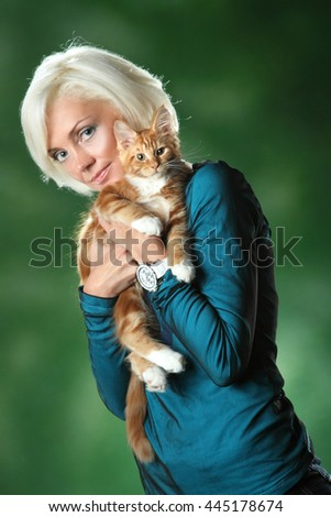 beautiful woman with a red cat. taking care of the animal. - stock photo