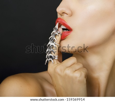 beautiful woman with a stylish silver claw ring on her finger (black background) - stock photo