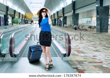 Beautiful woman with a suitcase on the airport - stock photo