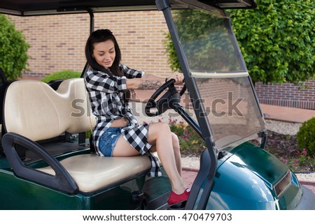 Beautiful woman with a tottoo in short jeans briefs is sitting on a green golf cart.