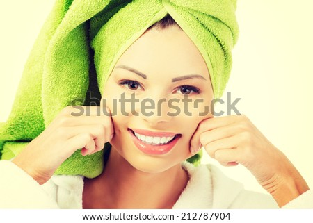 Beautiful woman with a towel on her head holding her cheeks, isolated on white - stock photo