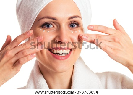 Beautiful woman with a towel on her head is applying cream under her eyes and smiling, isolated on a white background, close-up