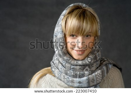 Beautiful woman with a white perfect smile and blue eyes in winter warmly clothed. Portrait of attractive beautiful young woman wearing scarf and winter cap, dark gray background - stock photo