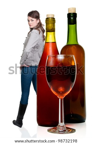 Beautiful woman with a wine glass and bottles of red wine. - stock photo