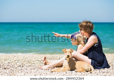 Beautiful woman with adorable daughter and terrier puppy resting on the beach - stock photo