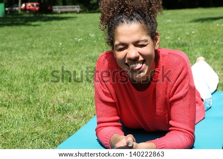 Beautiful woman with an afro doing yoga in the park