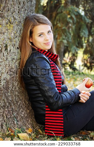 Beautiful woman with an apple sitting near a tree - stock photo