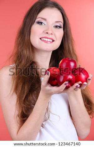 Beautiful woman with apples on pink background