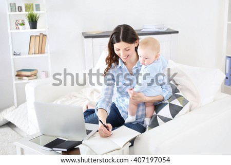 Beautiful woman with baby boy working from home using laptop - stock photo