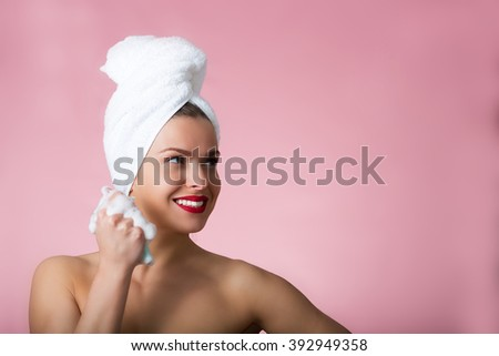 Beautiful woman with bath towel and soapy sponge - stock photo