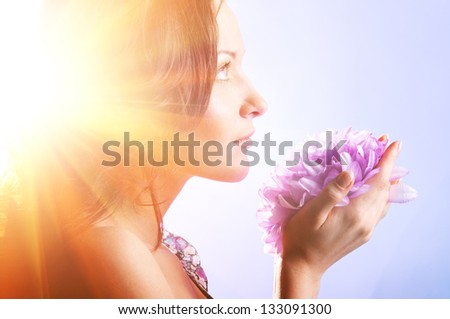 beautiful woman with big flower in sun rays