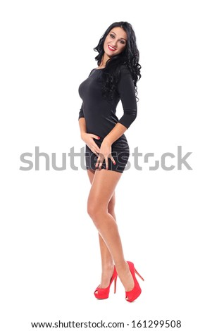 Beautiful woman with black curly hair and black dress and red heels is posing over a white background