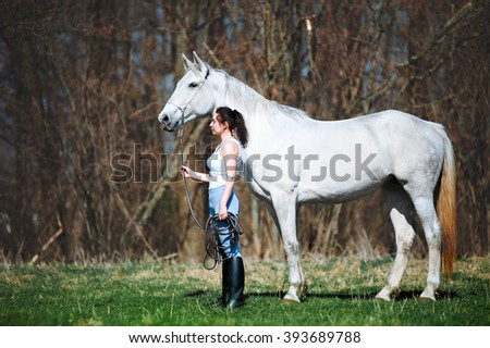 Beautiful woman with black hair stands near a horse and holding her cord. A girl and a white mare standing on a neutral pastel background - stock photo