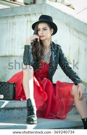 Beautiful woman with black hat, red dress and boots posing sitting on stairs. Young brunette spending time during autumn. Long hair attractive girl with creative makeup and red dress, outdoors shot - stock photo