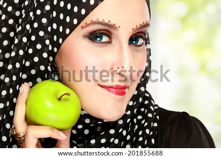 beautiful woman with black scarf holding green apple. diet concept - stock photo