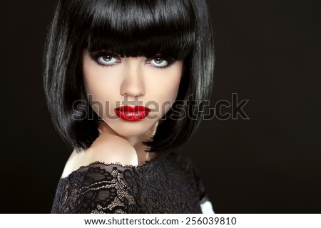 Beautiful Woman With Black Short Hair. Haircut. Hairstyle. Fringe. Professional Makeup. Lady isolated on black background. - stock photo
