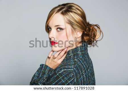 beautiful woman with blond hair in a bun wearing a tweed jacket and red lipstick on grey studio background - stock photo