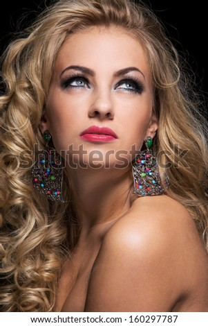 Beautiful woman with blonde curly hair posing with her shoulders naked over a black background