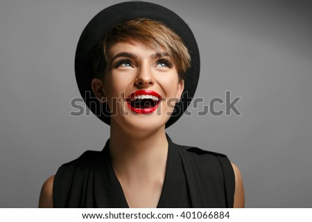 Beautiful woman with blue eyes and red lips is very happy to pose on camera. - stock photo