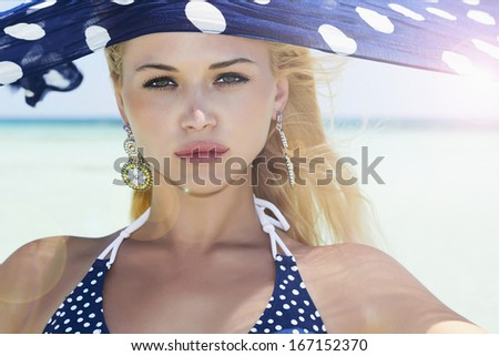 Beautiful woman with blue shawl on a beach. summer sunlight - stock photo