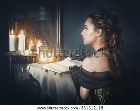 Beautiful woman with book in retro dress and ghost in the mirror