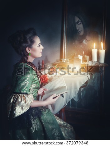 Beautiful woman with book in retro dress and ghost in the mirror - stock photo