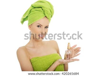Beautiful woman with bottle of perfume. - stock photo
