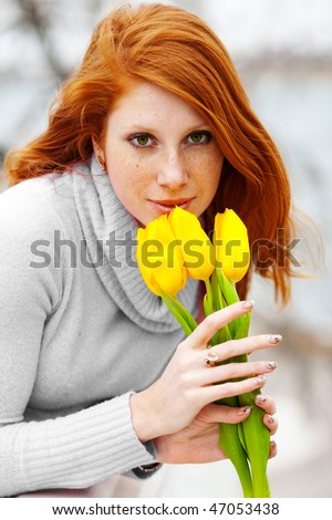 Beautiful woman with bouquet of tulips walking outdoor - stock photo