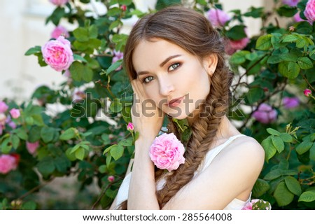 Beautiful woman with braids in garden with roses - stock photo