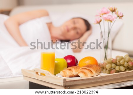 Beautiful woman with breakfast in bed early. woman sleeping in bed on white pillow - stock photo