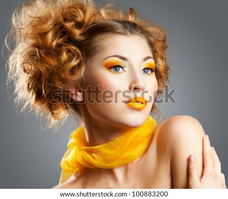 Beautiful woman with bright creative yellow makeup and curly hairstyle - stock photo